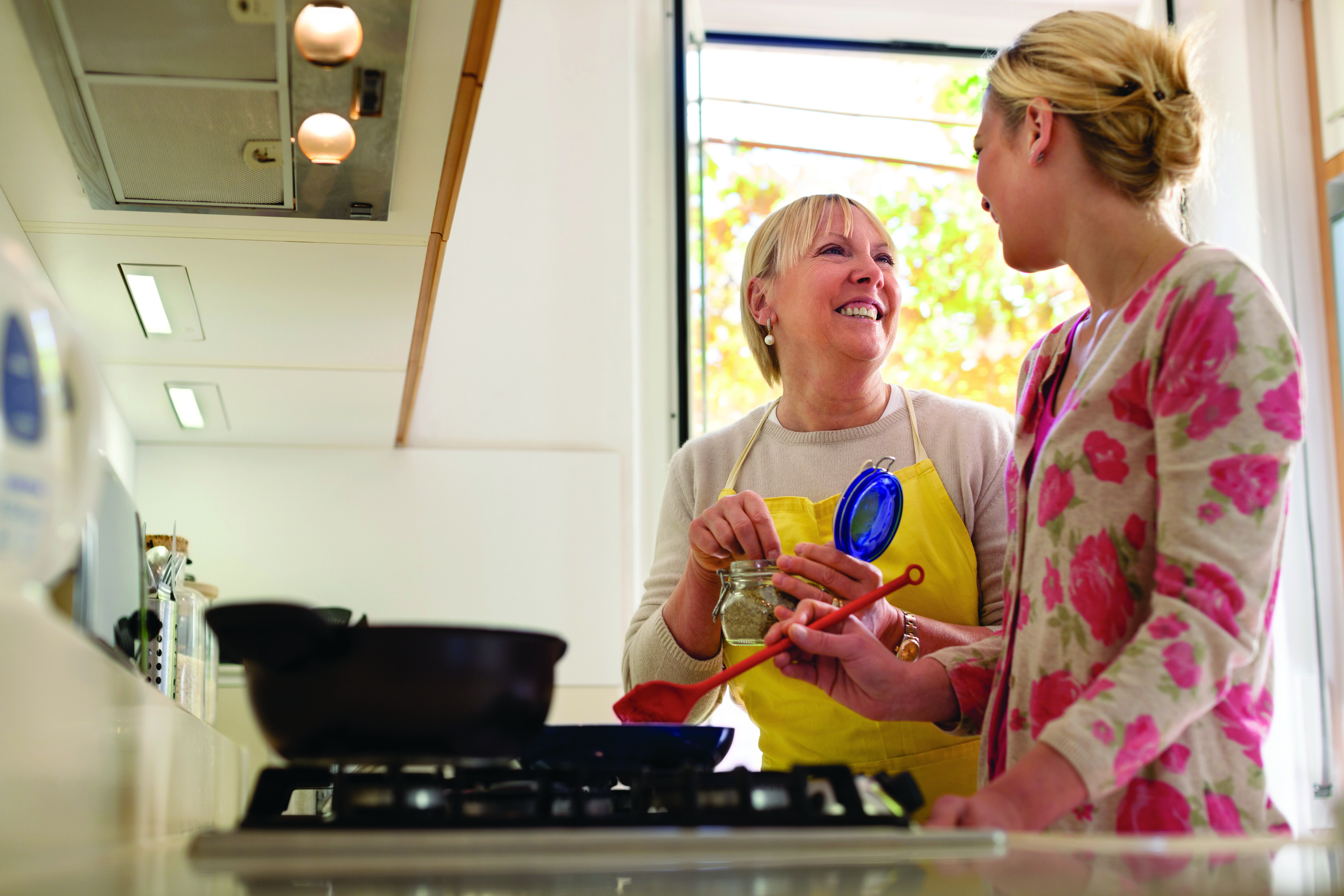 Two women talking while cooking a meal.